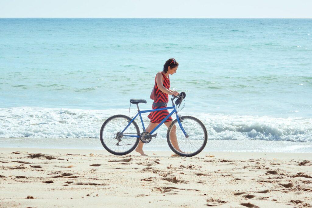 Radfahrerin durchquert Sand an Nordseeküste
